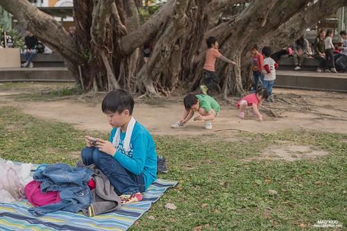 幾個孩子在後面玩沙爬樹,唯獨他一人對大地失去熱情,獨自玩著手機,肩頸痠痛的毛病從小就慢慢建立,每個人對照片或畫的見解不同,有時候是非常主觀的,這張照片看來像是悠閒的午後,看來我是比較悲觀的。