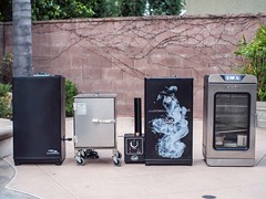 Best electric smokers lined up for comparison testing in the backyard patio area ready to smoke meats for weekend barbecue from masterbuilt, Smokin' It, Bradley, and Char-broil (yourbestdigs) Tags: woodchips tray smoking bisquettes chicken meat beef pork loin thigh leg bone sliced pulled boneless ribs smoker smoke smoked loader display digital butt dripping grease dry rub marinated marinate marinade char broil broiler broiled black glove cleaning outside patio bbq chip burger breast cook cooking cooked chef oven bake baked fried moist skinless cedar oak cypress straw hay pine needles bark colored mulchbarbecue hickory charcoal ash hardwood chippings chipping bradley charbroil smokin it masterbuilt master