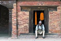 0765 The Flower Wreaths Salesman (Hrvoje Simich - gaZZda) Tags: man salesman wall brick outdoors flowers wreath orange red travel kathmandu nepal asia nikon nikond750 nikkor283003556 gazzda hrvojesimich