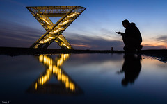 So close and yet so far (Eifeltopia) Tags: saarland saarpolygon ensdorf denkmal steinkohlebergbau mining puddle reflection planet venus person architecture bluehour coal monument small dot duhamel bergwerk skulptur sculpture abstract water hands ribbon triangle dreidimensional threedimensional symbol symmetrie astro hill mountain berg hügel stairway lights illiminated coalmining abendhimmel morgenstern abendstern sisterplanet morningstar eveningstar germany x beanie vieleck brancoconsdorf