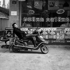 Laziness allowance (Go-tea 郭天) Tags: hangzhoushi zhejiangsheng chine cn candid portrait hangzhou linan young man lazy alone lonely nap rest resting delivery motorbike motorcycle sun sunny shadow glasses tired boy parked duty street urban city outside outdoor people bw bnw black white blackwhite blackandwhite monochrome naturallight natural light asia asian china chinese canon eos 100d 24mm prime