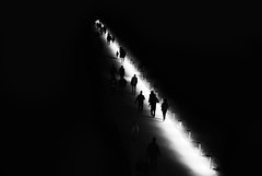 a luminous road (nancy_rass) Tags: road path street light luminous people commotion shadows silhouette dark night line leading monochrome black white grayscale contrast high