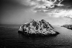 Small island on a snowy day (PeterSundberg66 former PeterSundberg65) Tags: island pier lighthouse norway hurtigruten water dark clouds black white fjord landscape sea sky rock ocean boat mountain monochrome sand