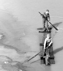 In the river (theirhistory) Tags: children boys kids trousers coat jacket wellies rubberboots river plank water
