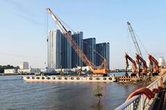 . (Out to Lunch) Tags: 2nd thu thiem bridge saigon river ho chi minh city vietnam rapid urbanization urban cranes highrises sky water architecture fuji x100t 235mm