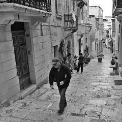 Malta Streets (Douguerreotype) Tags: candid people balcony monochrome blackandwhite steps malta buildings street mono architecture city stairs urban bw door