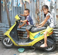 playing motorcycle (the foreign photographer - ฝรั่งถ่) Tags: two children boy girl yellow motorcycle khlong thanon portraits bangkhen bangkok thailand canon