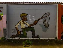The Poacher (Steve Taylor (Photography)) Tags: net trout fish poacher smoking va boots cap oruapaeroa graffiti mural streetart grey green brown man newzealand nz southisland canterbury christchurch newbrighton northnewbrighton weeds