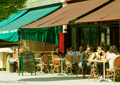 Cafe Life 24 (M C Smith) Tags: men women tables chairs red green blue pavement signs letters numbers pentax k3ii white fruit veg cafe shops eating drinking sunglasses awnings board bin black liner drinks tree shade light orange shadow symbols