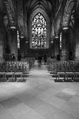 St Giles Cathedral with Norman March 2018 (7 of 50) (Philip Gillespie) Tags: edinburgh scotland st giles cathedral street photography architecture canon 5dsr stained glass windows chairs ceiling old ancient candles angles lines dark floor shadows light day sky sun sunny spring reflections colour green blue red orange yellow mono monochrome black white organ dog shadow long exposure christ religious church chapel indoor interior praying pray service triangles squares clouds feet legs arms hands flame fire