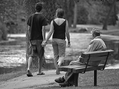 Love begins with a smile, grows with a kiss, and ends with a teardrop. (Paul Linton) Tags: park old blackandwhite bw canada man love bench walking holding hands couple winnipeg manitoba lonely