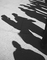 Line Up (One Foot Over The Moon) Tags: shadow people blackandwhite bw lines waiting purse anticipation gravel patience activities gravelroad outtings cidarmill