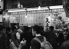 """delicious food ... 臭豆腐 (stinky tofu) ... oh"" (hugo poon - one day in my life) Tags: nikonfa nikon50mm kodak film tmax400 hongkong mongkok tungchoistreet sunday afternoon eating stinkytofu two girl delicious vanishing sign shop crowd people food kowloon"