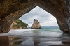 Through the looking hole (Nikhil Ramnarine) Tags: newzealand northisland coromandel cathedralcove seastack cave reflections framed sea headland clouds