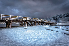 Winter Bridge (Paul Rioux) Tags: scenic seashore waterfront beach winter snow snowfall cold ice frost calm water sea ocean reflection sky morning clouds outdoors prioux esquimaltlagoon colwood westshore blue trees bridge structure