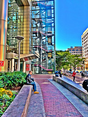 (Scorpiol13) Tags: crowded busy street baggage tourists walking standing sitting cement brick pavement walkway sidewalk daylight plants flora garden trees skyscraper stairs shapes angles lines geometry metropolitan urban hdr colorful landscape people reflection windows glass concrete structure buildings outdoors southstation boston streetphotography city