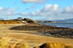 Love the Welsh coastline. (alex.vangroningen) Tags: wales sea mountains rocks castle sky clouds grass houses hotel handheld people water