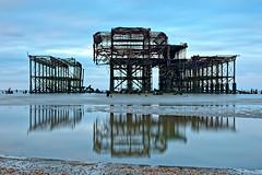 West Pier (Geoff Henson) Tags: sea ocean water reflection tide sand shingle pebbles sky clouds daybreak dawn pier structure abandoned rust decay ruin beach seascape blue 1500v60f