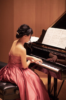 Beautiful woman playing piano in concert