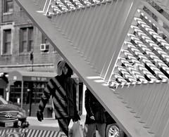 Along West 12 Street, by the AIDS Memorial In The Village (Striped) (sjnnyny) Tags: stevenj sjnnyny d750 nyc westvillagestreetphoto person manhattan aidsmemorialinthevillage west12street 7aveatgreenwichave bw mono afs85f18ged shadows shadestructure park neighbourhood locals