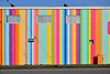 Never enough colour (James_D_Images) Tags: building painted stripes colour colours bright colourful frontlit sunny blue sky wires windows street sidewalk utility box orange red pink yellow magenta brown white roof vent shadow