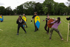Historia Normannis Meadows June 2018-404 (Philip Gillespie) Tags: historia normannis central scotland sparring fighting shields swords axes spears park grass canon 5dsr men man women woman kids boys girls arms feet hands faces heads legs shins running outdoor tabards chain mail chainmail helmets hats glasses sun clouds sky teams solo dead act acting colour color blue green red yellow orange white black hair practice open tutorial defending attacking volunteer amateur kneeling fallen down jumping pretty athletic activity hit punch