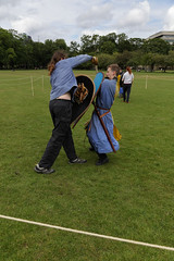 Historia Normannis Meadows June 2018-49 (Philip Gillespie) Tags: historia normannis central scotland sparring fighting shields swords axes spears park grass canon 5dsr men man women woman kids boys girls arms feet hands faces heads legs shins running outdoor tabards chain mail chainmail helmets hats glasses sun clouds sky teams solo dead act acting colour color blue green red yellow orange white black hair practice open tutorial defending attacking volunteer amateur kneeling fallen down jumping pretty athletic activity hit punch