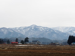 There are snow covered mountains in the background (murozo) Tags: akita nairiku juken railway local train snow mountain rice field tree senboku japan 秋田内陸線 秋田内陸縦貫鉄道 ローカル線 列車 雪 山 田圃 木 仙北 日本