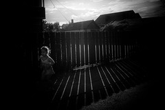 sunset run (Pomo photos) Tags: girl run sunset fence black blackandwhite blackwhite bw mono monochrome sun shadow shape shapes roof house building hair clouds cloud sky epl8 olympus mood moody kid child wall pomo pomophotos weather paysage town candid olympus15mm