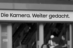 Die Kamera. Weiter gedacht. (Pascal Volk) Tags: berlin mitte alexanderplatz berlinmitte werbung advertising publicidad artinbw schwarz weis black white blackandwhite schwarzweis sw bw bnw blancoynegro blanconegro spring frühling primavera canoneos80d canonef24105mmf4lisusm 93mm dxophotolab