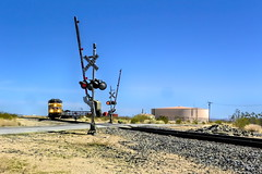 The Oncoming Train (joe Lach) Tags: railway crossing railroad train union pacific freight yellow blue green red water storage tracks signal mojave desert mohave antelope valley joelach nowhere themiddleofnowhere