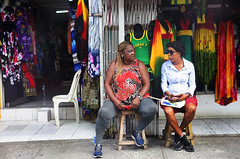 Likkle Shops Pon Di Strip (Poocher7) Tags: people portrait shopkeepers ladies shopping mobay downtown montegobay shops dresses sitting chatting talking irongates sunglasses stools jamaica caribbean westindies socksandsandals braids sweatpants shorts discussingbusiness streetphotography