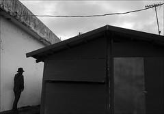 F_47A1603-1-BW-1-Canon 5DIII-Tamron 28-300mm-May Lee 廖藹淳 (May-margy) Tags: maymargy bw 黑白 心情的故事 人像 portrait 逆光 backlighting 背影 viewfromback 剪影 silhouette 房屋 buildings 鐵皮屋 metalshed 天線 antenna 白牆 white wall 鎖門 locked door 電線 power line 方形 rectangle 三角 triangle 直線 straight 烏雲 dark clouds 台東縣 台灣 中華民國 taiwan repofchina 街拍 streetviewphotography 線條造型與光影 linesformandlightandshadow 天馬行空鏡頭的異想世界 mylensandmyimagination 心象意象與影像 naturalcoincidencethrumylens 幾何構圖 點人 humaningeometry f47a16031bw1 taitungcounty canon5diii tamron28300mm maylee廖藹淳