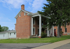 Caesar Magruder House — Somerset, Ohio (Pythaglio) Tags: somerset ohio perrycounty historic house dwelling residence caesarmagruder ihouse fivebay twostory brick flemishbond classicalrevival 1830s 11windows stone lintels sills atticwindows chimney cornicereturns dentils portico ionic columns volutes capitals addition tree bluesky clouds per1604