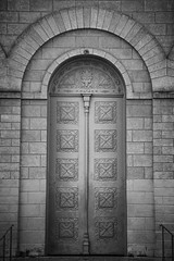 A beautiful door of a Roman Catholic church from a small town in Minas Gerais, Brazil. A black and white image enphasize the texture of the wood of the door and the stones of the wall. (pedroferr) Tags: stone arch landscape dramatic pray cloudy church minasgerais wood vintage southamerica desaturated bw clouds religion exterior door contrast classic catholic travel architecture brazil wooden trip holy jesus blackandwhite leopoldina god
