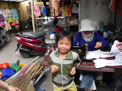 Tam Ky-1F-April 2010 078 (PDC Global) Tags: pdc sewing sew machine clothes clothing sempstress job brooms motorcycle bike scooter bicycle culture kid youth young child children kids joy happiness smiling smile smiles happy joyful fun hat hats cap caps tamkỳ tamky vietnam 2010