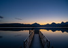 Sunrise Lake McDonald Dock (Kevin VanEmburgh Photography) Tags: explore glacier glaciernationalpark kevinvanemburghphotography montana mountains nationalpark nature travel dock pier water lake standingwater mountainsandclouds reflection still calm sunrise firstlight bluesky earlymorning
