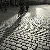 Bicycles on cobblestone (Bernhardt Franz) Tags: fahrrad cyclist bicycle cobblestone kopfsteinpflaster shadow schatten münster prinzipalmarkt people menschen blackandwhite bw street gegenlicht contralight city urban stadt