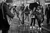 Get a Photo of the Busker (garryknight) Tags: sony a6000 on1photoraw2018 london allrightsreserved themonoseries monochrome blackandwhite 50mmf18 bricklane street candid umbrella people woman photograph smartphone phone mobile cellphone busker performer streetperformer guitarist singer microphone rain rainy weather