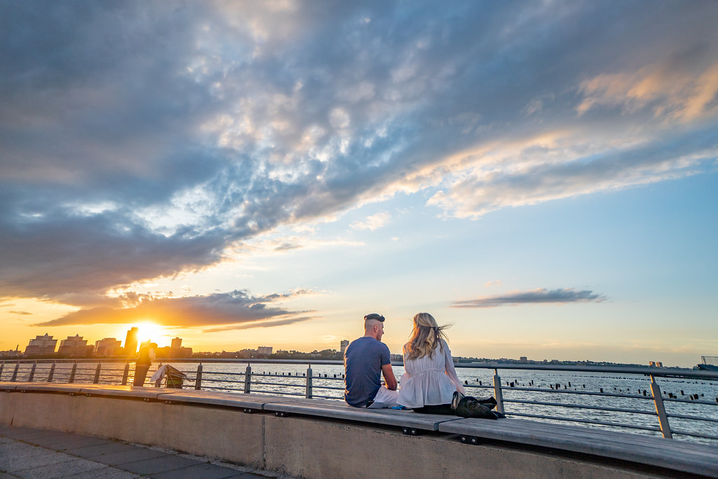 A couple enjoying the New York sunset along one of New York's many piers along the Hudson River.