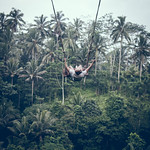 BALI, INDONESIA - DECEMBER 26, 2017: Man having fun on the swing with action camera in the jungle of Bali island, Indonesia. Rainforest, swing. thumbnail
