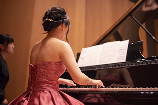 Young female musician playing piano in concert