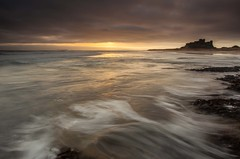 Bamburgh Dawn (Julian Barker) Tags: bamburgh castle northumberland north east england uk budle bay great britain british heritage english europe sun sunrise dawn sea shore seashore coast ocean wave action swash rocks sky motion blur canon dslr 5d mkii julian barker