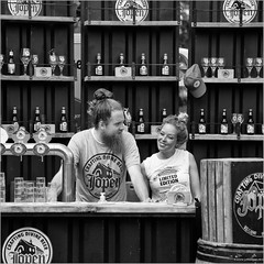 Limited edition (John Riper) Tags: johnriper street photography straatfotografie square vierkant bw black white zwartwit mono monochrome netherlands candid john riper rotterdam canon 6d 24105 bar stand spirits boy girl smile cap beer drinks fopen