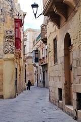 Malta Streets (Douguerreotype) Tags: statue city people street balcony stone buildings malta architecture urban door lamp