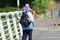 Park Flautist (Bob Hawley) Tags: asia taiwan kaohsiung metropolitanpark outdoors nikond7100 nikkor35135mmf3545lens people women bridges musicalinstruments flutes flautists