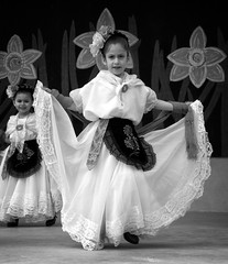 Center Stage (Anne Worner) Tags: anneworner blackandwhite daffodilfestival hispanic olympus roundrock silverefex texas bw background candid children daffodil dancing dresses entertaining flowers girls group happy heritage lace monochrome stage streetphotography people performance cultural girl younggirl braidedhair brooch necklace backdrop embroidery dress candidstreetphotography naturallight daylight