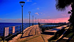 Blue Water, Pink Sunset - Limassol, Cyprus (Andreas Komodromos) Tags: beautiful blue boardwalk city clouds colorful cyprus eu europe lights limassol mediterranean nyandreas pier pink sea serene shadow sky spectacular streetlights sunset trees water waterfront landscape seascape sony6000 travel shadows dusk evening afternoon waterway walkway