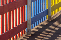 Fence in primary colors (Jan van der Wolf) Tags: map181186vv fence hek shadow shadowplay schaduw schaduwspel shadows red yellow geel primarycolors composition colors colours perspective perspectief rhythm herhaling repetition visualrhythm ritme