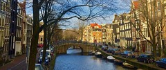 City Charm (Rnoltenius) Tags: amsterdam beauty canal life parked cars bicycles sun rooftops mustard red vibrant ripples water ambience gouda travelteq
